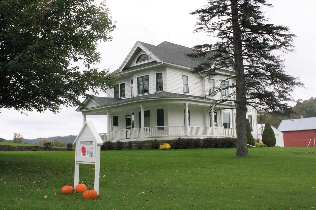 First time on the market!  Don't miss out on this incredible hobby farm just a few minutes from Galesville.  Built in 1915, this Queen Anne style home is recognized by the Wisconsin Historical Society. Main floor offers grand foyer(stunning staircase, stain glass window); formal living room(original wide woodwork); family room/music room; formal dining room(built-in hutch); functional kitchen(appliances included); full bath.  Upper offers 4 well proportioned bedrooms, office space plus additional full bath & scenic views from upper balcony. Additional features-full basement(updated breakers & boiler), wrap around porch, covered patio, 80x45 pole barn, garage, barn plus historic outbuildings, spacious lawn & meandering stream.  Enjoy this well maintained property located in a quiet setting.