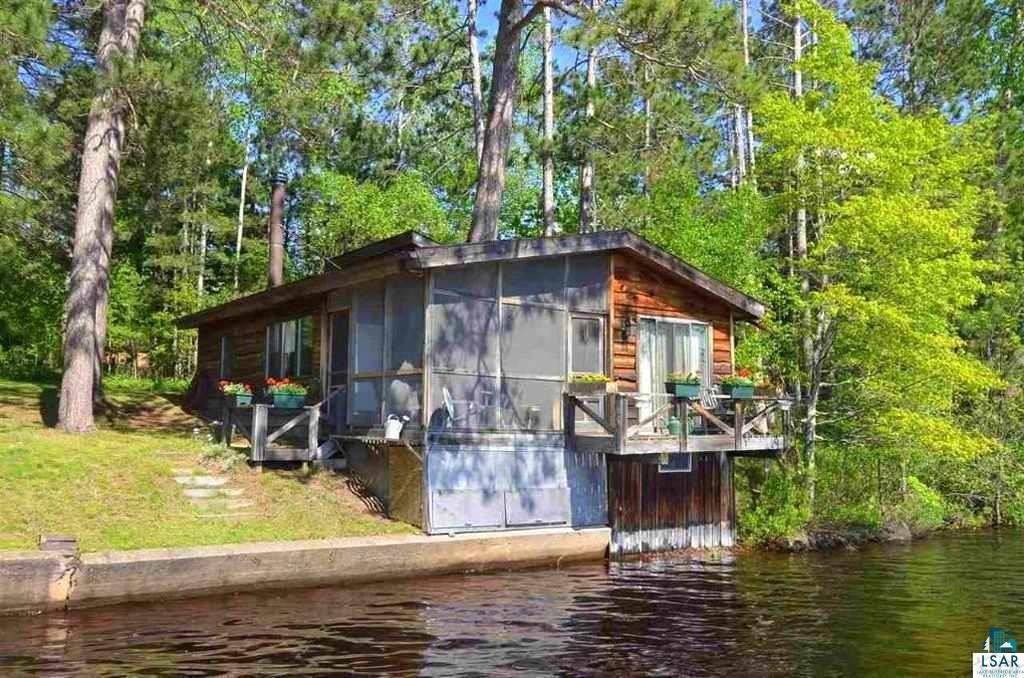 """The """"Eagles Nest"""" is an absolutely charming cottage.  It is uniquely positioned on water's edge so that you can have an unobstructed view of the lake and sunsets.  The cottage features an enclosed screen porch that surrounds a majestic red pine. It has two nice sized bedrooms and a den overlooking the lake that could be used as a guest room.  Concrete steps provide easy access to the lake which is known for its sandy bottom.  The interior walls are black ash.  Take the chill off the season with the wood stove located in the living room area.  The cottage also has electric heaters and the mini-split air conditioning has a heat pump.  This cabin is one-of-a-kind with 162 feet of frontage on Lake Minnesuing and the 2.6 acre site was recently surveyed."""