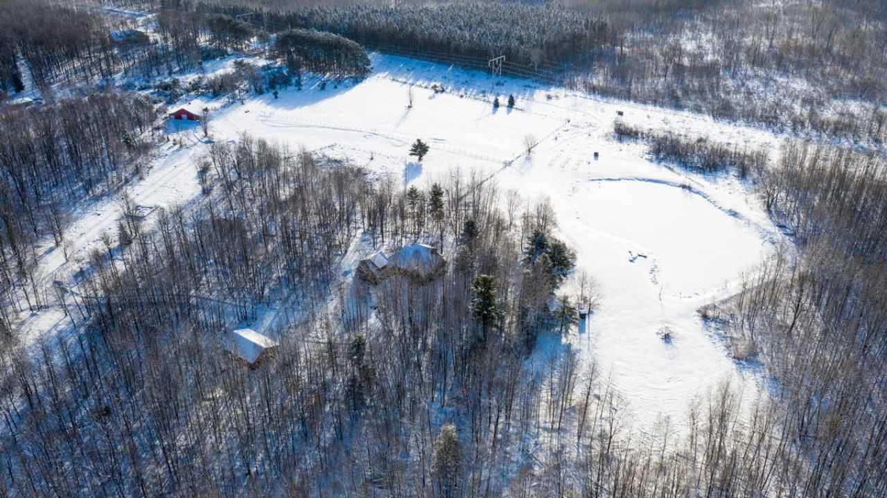 RARE OPPORTUNITY TO OWN 64+ ACRES MINUTES FROM WAUSAU THAT ABUTS COUNTY LAND/RINGLE MARSH FOREST. Amazing hunting, fishing, & recreation right in your own backyard with mature trees, large pond, newer 48x50 pole building ideal for horses w/four horse stalls, 30x42 insulated/heated workshop, & range land, & a nearly 5,000 sq ft quality-built, 4 bedroom, 3 1/2 bathroom, open concept home. Larry Meyer Construction remodeled the master bathroom, complete lower level, & constructed the pole building in 2011.,Sixty four plus acres have been nicely maintained and groomed and feature a fenced garden area, landscaping throughout, and trails to all corners of the property. The exterior of the home has multiple entertaining spaces including the front and back covered deck and side stone patio. There are many varieties of apple trees, a pear tree, and raspberry and blackberry plants along the trails on the property. A lot of work went into the exterior landscape and manicured trails! MAIN LEVEL: The front entrance offers a tiled entryway with wood-lined ceiling and an open staircase to the second-floor master suite. Kitchen features granite countertops, walk in pantry, under mount sink, with all appliances included. Off the kitchen is a tiled sitting area with beautiful views to the backyard. The tiled dinette offers a large dining space. All furniture is negotiable! The living room (420 sq. ft) features a wood-lined 9? ceiling with a ceiling fan and two sets of patio doors that lead to the covered deck and backyard pond. A large main level office(196 sq. ft.) features hardwood flooring, two-door-wide pocket doors and large windows let in great natural light. The main level bedroom (196 sq. ft.) has 11.5? ceiling with ceiling loft for bunk bed and a nearby full bathroom. Off the garage is a main level laundry room with sink, washer/dryer included, and a 1/2 bath for guests. From the garage entrance, there are stairs to an upper-level family room/ man cave (624 sq. ft) with knot